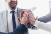 Photo cropped shot of professional  business team giving high five in office