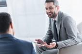 usměvavý mladý podnikatel drží digitální tabletu a při pohledu na mužský kolega na popředí