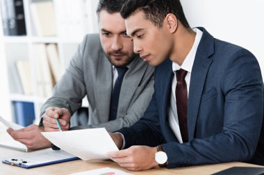 two focused businessmen working with papers in office