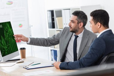 Bearded businessman showing desktop computer with trading graphs on screen to young colleague at workplace stock vector