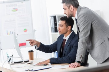 focused businessmen pointing with finger and looking at desktop computer in office