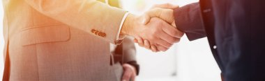 close-up partial view of businessmen in formal wear shaking hands in office