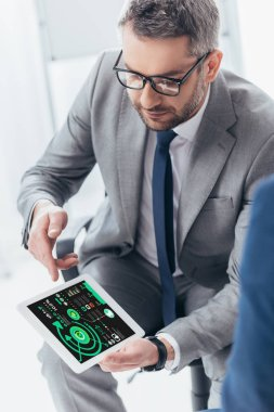 high angle view of handsome businessman in eyeglasses using digital tablet with charts and graphs on screen