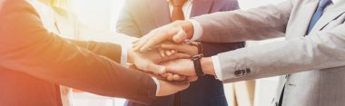 cropped shot of professional successful business people stacking hands together