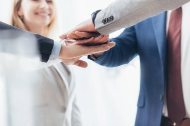 cropped shot of professional business people stacking hands together