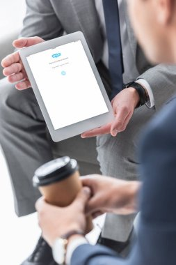 Cropped shot of businessman showing digital tablet with skype app to male colleague with coffee to go stock vector