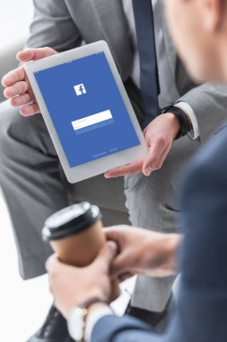 cropped shot of businessman showing digital tablet with facebook app to male colleague with coffee to go