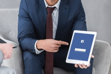 cropped shot of businessman in formal wear pointing with finger at digital tablet with facebook app