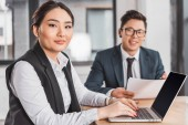 young asian business people smiling at camera while working with papers and laptop in office