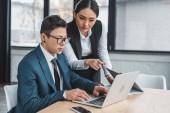 mladí kazašských podnikatelů společně pomocí přenosného počítače v kanceláři