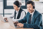 young man in headset looking at camera while working with female colleague in call center