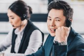 Photo handsome young man in headset smiling at camera while working with female colleague in call center