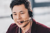young asian man in headset smiling at camera in office