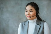 beautiful kazakh call center operator in headset looking away on grey