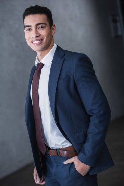 portrait of handsome young mixed race businessman standing with hand in pocket and smiling at camera