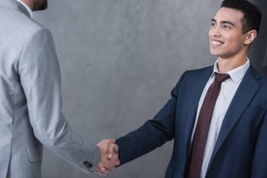 Cropped shot of smiling young businessman shaking hands with colleague on grey stock vector