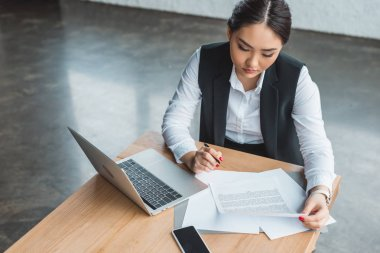 high angle view of young asian businesswoman working with papers and laptop in office