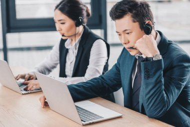 young call center operators in headsets using laptops in office