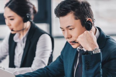 young call center operators in headsets working in office