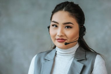 Beautiful young kazakh call center operator in headset smiling at camera on grey stock vector