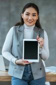 fiatal ázsiai üzletasszony gazdaság digitális tabletta-val üres képernyő és a kamera irodában mosolyogva