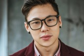 Fotografie close-up portrait of handsome young asian man in eyeglasses looking at camera