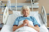 Fotografie Starší žena ležela v posteli se sepjatýma rukama a modlil se v nemocnici