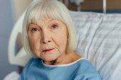 Fotografie selective focus of sad senior woman with grey hair lying in bed in hospital