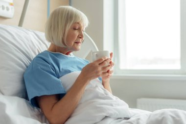 selective focus of senior woman lying in bed and drinking tea in hospital
