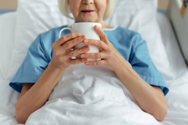 cropped view of senior woman lying in bed and drinking tea in hospital