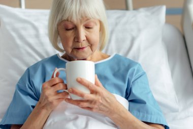 senior woman with grey hair lying in bed and drinking tea in hospital