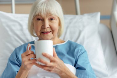 smiling senior woman lying in bed, looking at camera and drinking tea in hospital