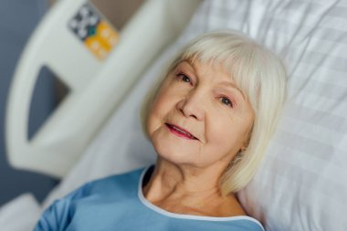smiling senior woman with grey hair lying in bed in hospital