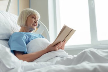 senior woman with grey hair lying in bed and reading book in hospital