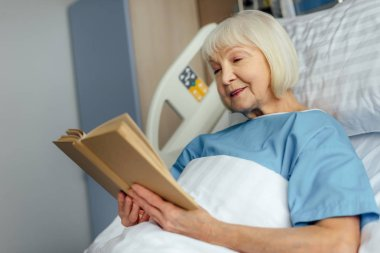 smiling senior woman with grey hair lying in bed and reading book in hospital