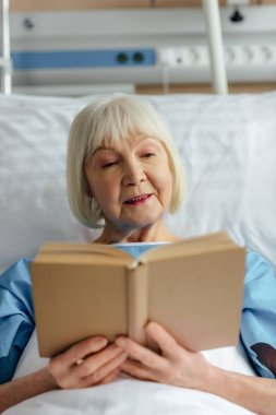 selective focus of senior woman with grey hair lying in bed and reading book in hospital