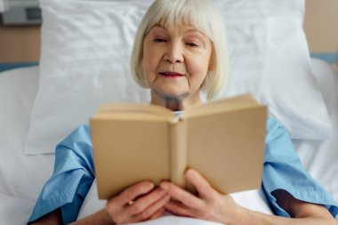 senior woman lying in bed and reading book in hospital