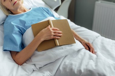 cropped view of senior woman with book sleeping in bed in hospital