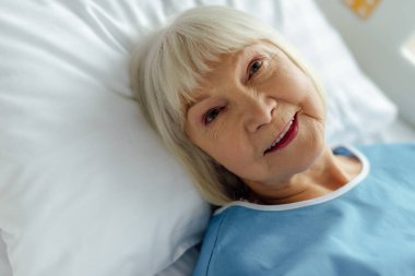 selective focus of smiling senior woman with grey hair lying in bed in hospital