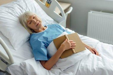 selective focus of senior woman with book sleeping in bed in hospital