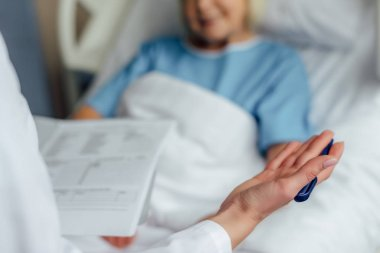 cropped view of doctor holding diagnosis and consulting patient lying in hospital bed