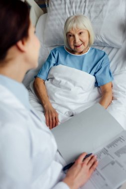 female doctor sitting on bed and holding diagnosis while senior woman lying in bed in hospital
