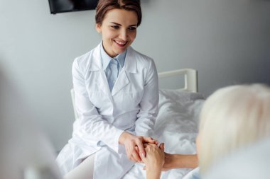 smiling female doctor holding hands with senior woman lying in bed in hospital