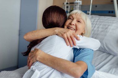 happy senior woman lying in bed and hugging female doctor in hospital