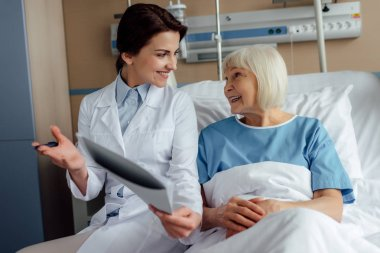 smiling female doctor holding diagnosis and consulting senior woman lying in hospital bed