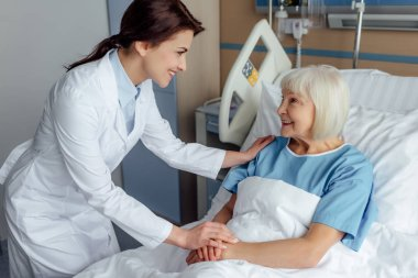 happy female doctor holding hands and consulting senior woman lying in hospital bed