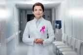 Ärztin mit rosa Schleife und gefalteten Händen Blick in die Kamera im Krankenhaus, Brust-Krebs-Bewusstsein-Konzept