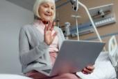 donna maggiore felice che si siede sul letto, utilizzando il computer portatile e agitando con mano pur avendo videochiamata in ospedale