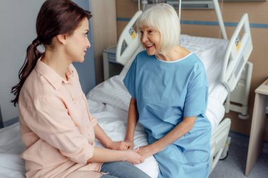 senior woman and daughter sitting on bed and holding hands in hospital