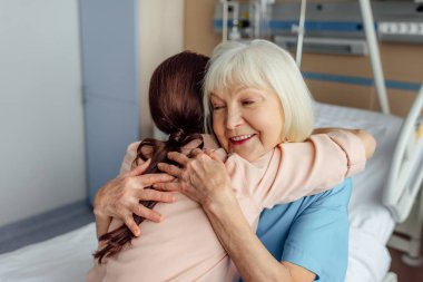 happy senior woman and daughter sitting on bed and hugging in hospital